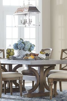 Our Lakeview rectangle dining table has a concrete top, double pedestal base and a driftwood finish with wire brushing. Its refined rustic appeal invites family and friends to gather around this dinner table.