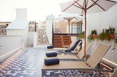 Terrasse au sol graphique et parasol blanc