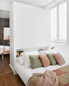 Madrid pastel apartment with headboard as room divider between bedroom and bathroomhttp://www.apartmenttherapy.com/10-diy-ways-to-divide-small-spaces-202566