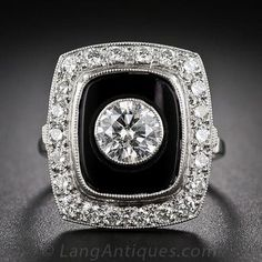 A bright-white and radiant round brilliant-cut diamond, measuring .85 carats, but due to the bezel setting, presenting all of one-carat, is set against a dramatic black onyx background, all of which are framed by bright and lively full-cut diamonds. This sparkling showpiece measures just shy of 3/4 inch high by 5/8 inch wide and is recently hand fabricated in platinum in faithful emulation of classic Art deco jewels from the 1920s. A beauty.