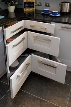 I've seen a  lot of corner cabinet storage ideas and most of them involve a lazy susan shelf. But this pull out drawer takes the cake