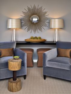 The plush silver-blue velvet chairs and light gray wall contrast beautifully with the bronze sunburst mirror, ottomans and toss pillows. Shimmery champagne lampshades bring it all together.