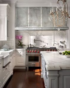 A classic white kitchen never goes out of style.  And I love how the grey center island complements the range, custom zinc hood, and veining in the marble. ✨ Simply stunning!! ✨✨ Design by #ObrienHarris