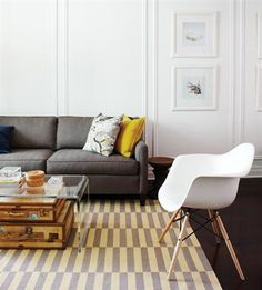 acrylic coffee table and white chair Again, clear table, graphic rug, mix of old and new, and a pop of color.