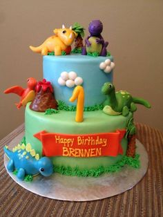 """Dinosaur theme birthday cake - Covered in MMF, all decorations made out of fondant. Grass is piped buttercream. Bottom cake is chocolate w/SMBC, top cake is white cake w/raspberry mousse filling. """"Could do a 1 layer and just choose 1 or 2 of the dinos"""" Dinasour Birthday Cake, Dinasour Cake, 3rd Birthday Cakes, Dinosaur Birthday Party, 1st Boy Birthday, Birthday Ideas, Dinosaur Cake Tutorial, Dino Cake, Birthday Cake Decorating"""