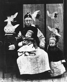 A three year old Puyi (right), standing next to his father (Zaifeng, Prince Chun) and his younger brother Pujie.