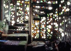 de la maison recyclée par Michael Reynolds Glass bottles catching the sunlight cast many hues in this beautiful Earthship interior.Glass bottles catching the sunlight cast many hues in this beautiful Earthship interior.