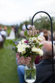 Outdoor fall wedding aisle marker idea - white, green and purple blooms hanging in glass vases {Laura Hollander Photography}