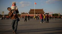 A man and child walk in Beijing's Tiananmen Square. China's government recently announced an easing of the country's one-child policy. While...