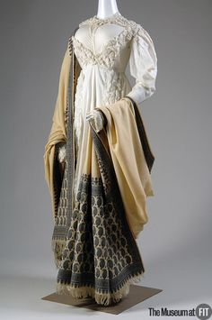 White cotton 1820. English. FIT. ostentatious sartorial displays of wealth unpopular after the French Revolution.The Spencer jacket and skirt, though retaining the typical high waist and general columnar silhouette of the first two decades, begins to show the increasing decoration characteristic of the 1820s. Kashmiri shawls were popularized by Empress Josephine. Imported shawls were prohibitively expensive, and European cities, like Paisley, like this one, made less costly shawls in…