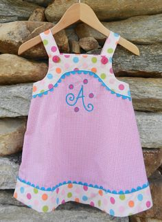 This colorful number has adjustable straps with bright pink buttons in the front. Pink gingham and contrasting circus dots are pulled together with aqua ricrac and our curly dot initial embroidery. Sizes: 9m, 12m, 18m, 24m, 2t, 3t & 4t. Was: $57 Now: $26 (+5 for the initial embroidery).