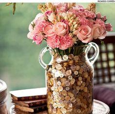 Dentro da ânfora, coloque um punhado de botões de madrepérola. Em seguida, encaixe um vaso menor com rosas, cravos e angélicas.