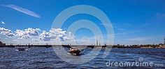A boat trip by wide Neva river of Saint Petersburg under blue summer sky with bright clouds.