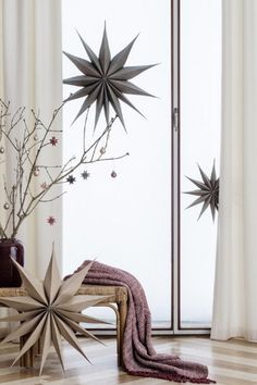 Hier schmücken grosse Papiersterne das Fenster, kleinere baumeln von trockenen Ästen in einer Vase, alles von Broste Copenhagen.