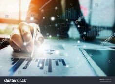 Close up Businessman hand holding pen and pointing at financial paperwork with financial network diagram.