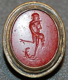Gryllos : Red jasper gem engraved with a figure with a head composed of two conjoined human heads, and a body composed of a human face, a ram's head, and bird's legs; in the ram's mouth is an ear of corn. On the ground is a lizard.