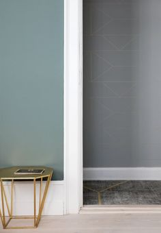 Blue-green colored wall and a hallway with patterned wallpaper in grey and gold.