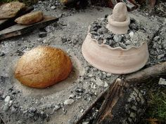 A loaf of Roman bread and a clay testum. The testum is placed over the bread and covered with coals. This helps produce even heat and holds in the moisture for portable bread baking.