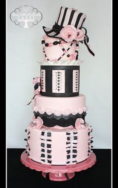 """The cake features various fondant ruffles, billowing and bows seen on the fabric of the dress as well as hand-painted details, sugar beaded necklaces, and fondant fabric flowers. The cake is topped with a striped hat with a hand molded brim adorned with more ribbons, bows, and fabric ruffled flowers.    .    This cake won First Place and Best in Division at the 2012 CO ICES Sweet Times in the Rockies Sugar Art show!    -- """"What sweet dreams are made of,"""" www.threelittleblackbirds.com"""