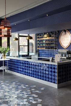 On the floor of this modern cafe simple concrete screed flooring has been combined with custom blue and white hexagon tiles decorated with the cafe s logo Coffee Shop Interior Design, Italian Interior Design, Coffee Shop Design, Cafe Design, Design Design, Modern Restaurant Design, Blue Cafe, Pub Decor, Modern Flooring