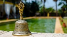 Antique brass bell by the pool at Sur La Mer, north Goa. TO ENQUIRE OR BOOK: https://www.tripzuki.com/hotels/sur-la-mer-goa/