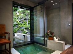window/door that opens up from a master sunk in bath to an outdoor pool and garden