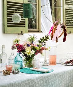 Glass bottles, flowers and feathers for pretty Summer garden party table decorations