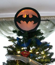 Christmas Tree 2013 detail - Bat-Signal tree topper! Cardboard hatbox, painted black, with cutout of bat-symbol in front, backed with cellophane. Inside is a yellow LED bulb, and box is lined with aluminum foil to help bounce light around. Electrical-safe - none of the electrical components touch metal or cardboard, and LED bulbs don't burn hot. Inserted Xmas village house accessory cord, and replaced incandescent bulb with a yellow LED one.