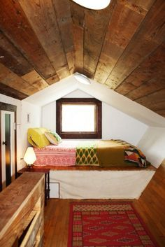 I love the coziness of the bed, the wood on the ceiling, the contrast between the white and the wood.