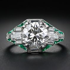 handmade platinum diamond ring, circa 1930s, features a geometric array of baguette diamonds outlined by fancy, custom-fitted, bright crystal green calibre emeralds. The side gallery of the ring is adorned with an elegant combination of straight up and down and flowing feminine scrolled openwork. Hand engraved flourishes at the top of each shoulder adds the finishing touch to this astonishingly beautiful, original Art Deco jewel.
