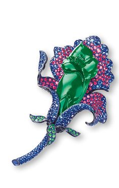 JADEITE AND GEM-SET 'FLOWER' BROOCH Modelled as a flower, centring on a carved jadeite of translucent deep emerald green colour, decorated by petals set with circular-cut sapphires and purplish-pink sapphires, accented by leaves set with tsavorite garnets, mounted in titanium and 18 karat white gold.  Plaque approximately 43.07 x 19.49 x 6.50mm.
