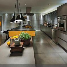 Graue Rechtecke durchziehen die Küche an Boden und Wand. Sowohl die Fliesen als auch die Möbel formen rechteckige Felder, die durch gelbe Elemente am Tisch und…