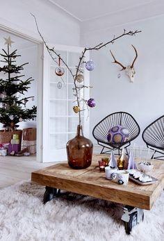 Een oude glazen fles met een mooie tak met daar aan decoraties. Je kunt hem versieren naar smaak en er een opvallend object van maken.
