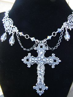 Magnificent cross pendant flanked by Swarovski bicones & teardrop crystals with lacy bead caps & filigreed stations. All with flowers & ribbons & layered in sterling silver! $20