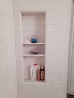 Shower niche with shelves. White subway tile with White Carrara marble tile shelves.