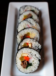 Korean Kimbap Rolls--Unlike Japanese sushi rolls, kimbap rice is typically seasoned with sesame oil and salt and is usually filled with egg, beef, carrots, spinach, pickled daikon and other ingredients.
