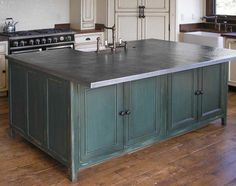 this island really looks like a stand alone piece of furniture.  love the zinc countertops and distressed finish of the cabinetry.