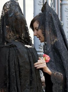 In Spain, women often wear a lace or silk vail over their head/shoulders called a mantilla. Often they wear a peineta with it (like a high comb) as shown in this picture.  It is also associated with a religious practice in the Roman Catholic Church. The lace mantillas became popular in the 18th/19th century. They're worn during Holy Week, bullfights, weddings, and other occasions. #2B
