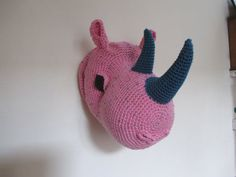 Big rhino head to be hanged directly with a ring at the back.  Crocheted with soft acrylic yarn, pink color.  Horns are dark blue-grey. Brown eyes  Can be washed by hand like a pillow  Size 35 cm more or less 14 inches