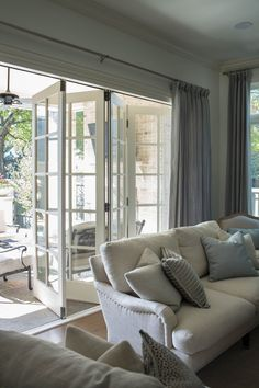 Accordion doors in family room leading out to the patio. English roll arm sofa. Neutral color palette. Accordian Door, Modern Garage Doors, Porch Enclosures, Casa Ideal, Exterior Doors, Glass Panel Door, Sliding Glass Doors, Panel Doors, Glass Panels