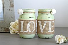 Two decorative Mason Jars in Celery Green . Each jar is hand painted & distressed, decorated with natural burlap with...