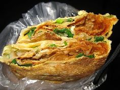 Jian bing (Chinese street food). Fried egg on a crepe with cilantro, green onion, garlic and hoisein sauce.