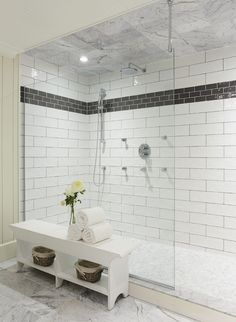bathroom with walk-in shower tiled with large white tile laid in a staggered pattern with an accent band of black subway tile (notice the different colored grout). The shower floors are tiled with marble hex floor tiles.
