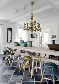 Loving the mismatched colorful chairs in the white kitchen.