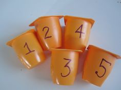 "Simple numbered yoghurt pots for the water tray (with holes punched out to match the number) ("",)"