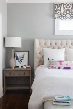 Chic bedroom features a cream linen tufted wingback headboard on bed dressed in white linen bedding as well as pink and purple lumbar pillow placed under a window dressed in Schumacher Chenonceau Charcoal Fabric situated next to a 1 drawer wood nightstand and a tall taupe lamp.