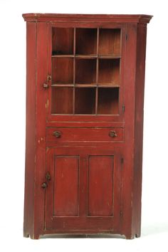 "OHIO CORNER CUPBOARD.  Second quarter-19th century, pine. One-piece cupboard with a nine-pane door over a drawer over a paneled door. Old red paint. 80""h. 45""w. 22""d., requires a 31"" corner."