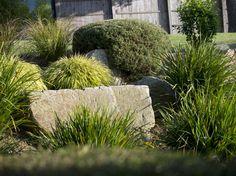 Là encore, le jeu entre les formes des végétaux et des minéraux est évidente : bloc de pierre presque carré, touffes de graminées et arbustes taillés en topiaire se jouxtent harmonieusement.