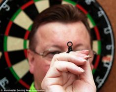 Stuart Needham shows off DartSight, a finger ring 'sighter' designed to help darts lovers hit 180s and the bullseye more often. RIGHT!