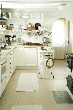 Light cabinetry with chunky dark accents (farmhouse light fixtures, appliances, items on shelves)
